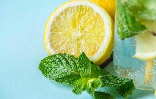 limone tagliato a metà, menta e un bicchiere d'acqua